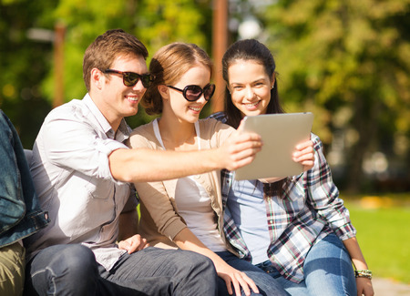 summer, internet, social networking and teenage concept - group of teenagers taking photo with tablet pc outside photo