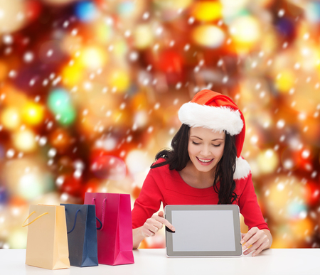christmas, x-mas, electronics, gadget concept - smiling woman in santa helper hat with blank screen tablet pc and shopping bags photo