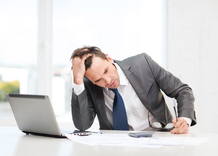 business, office, school and education concept - stressed businessman with laptop computer, papers and calculator Stock Photo
