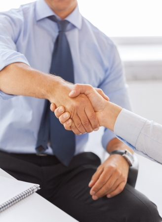 businesss and office concept - two businessmen shaking hands in office photo