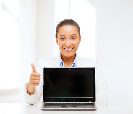 education,business, technology and internet concept - smiling woman with laptop computer photo