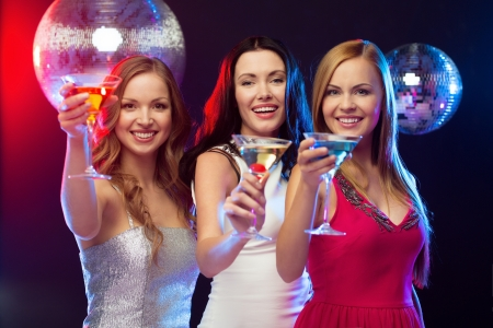 bachelorette party: new year, celebration, friends, bachelorette party, birthday concept - three women in evening dresses with cocktails and disco ball Stock Photo
