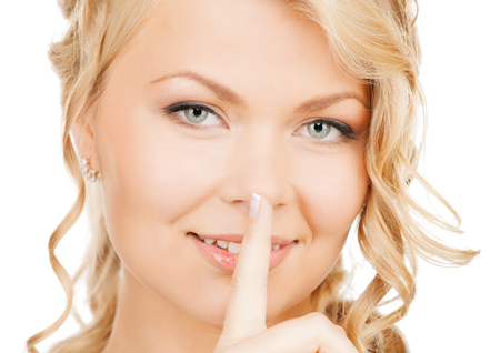 business, communication concept - picture of mysterious woman with finger on her lips photo