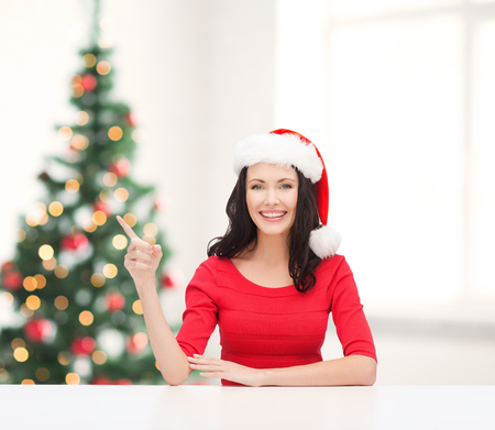 christmas, x-mas, winter, happiness concept - smiling woman in santa helper hat pointing to something photo