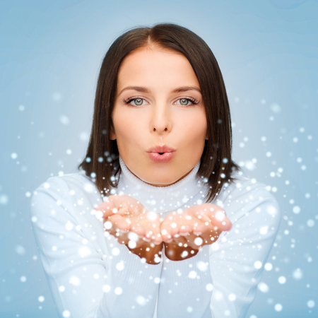 winter, people, happiness concept - happy woman in white sweater blowing on palms photo
