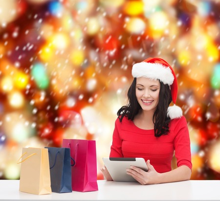 christmas, x-mas, online shopping, electronics concept - smiling woman in santa helper hat with shopping bags and tablet pc computer photo