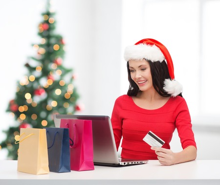 christmas, x-mas, online shopping concept - woman in santa helper hat with shoopping bags, laptop computer and credit card photo