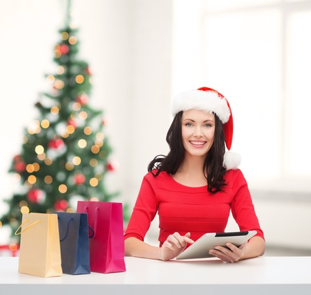 christmas, x-mas, online shopping concept - smiling woman in santa helper hat with shopping bags and tablet pc computer photo