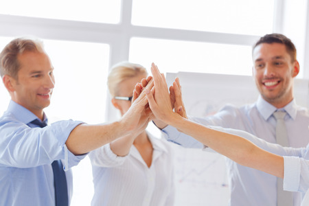 high five: success and winning concept - happy business team giving high five in office