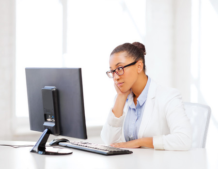 internet  concept: business and internet concept - african businesswoman with computer in office
