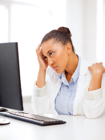 confused woman: business, office, school and education concept - stressed african businesswoman with computer at work