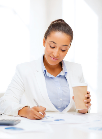 business, office, school and education concept - businesswoman with documents and takeaway coffee photo