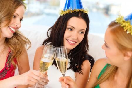 despedida de soltera: celebración, bebidas, amigos, despedida de soltera, cumpleaños concepto - tres mujeres sonrientes con sombreros de color azul con una copa de champagne