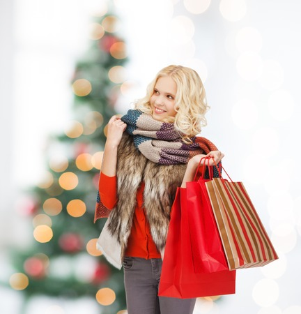 retail and sale concept - happy teenage girl in winter clothes with shopping bags photo