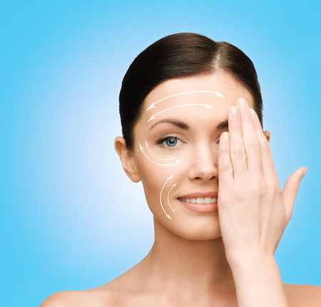 beauty, spa and health concept - smiling young woman covering half of face with hand photo