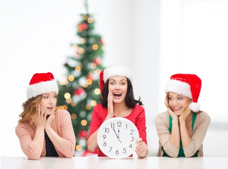 helpers: christmas, x-mas, winter, happiness concept - three smiling women in santa helper hats with clock showing 12