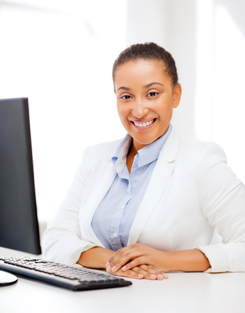 business and internet concept - smiling african businesswoman with computer in office photo