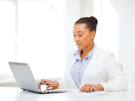 business and technology concept - african businesswoman with laptop writing something in notebook photo