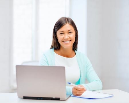 bedrijfsleven, onderwijs en technologie concept - asian zakenvrouw of student met laptop en documenten in het kantoor