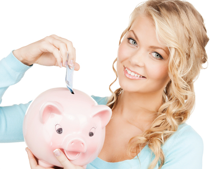 buisness, banking and savings concept - happy businesswoman puts cash money into big piggy bank photo