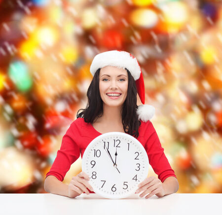 christmas, x-mas, winter, happiness concept - smiling woman in santa helper hat with clock showing 12 Stock Photo - 23977089