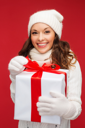 christmas, x-mas, winter, happiness concept - smiling woman in white clothes with gift box photo