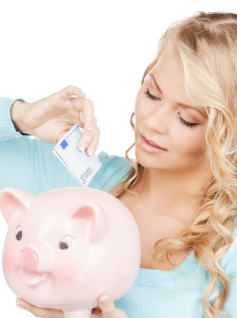 buisness: buisness, banking and savings concept - happy businesswoman puts cash money into big piggy bank Stock Photo