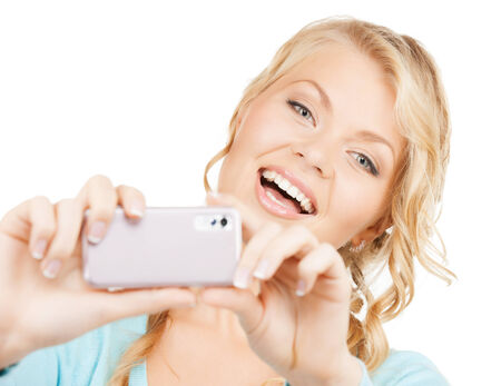 technology concept - smiling woman taking photo with smartphone photo