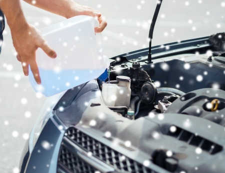 antifreeze: transportation and vehicle concept - man opening car bonnet and filling windscreen water tank with washing liquid Stock Photo