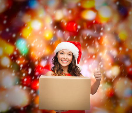 christmas, x-mas, winter, happiness concept - smiling woman in santa helper hat with parcel box showing thumbs up photo