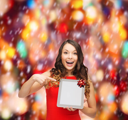 christmas, x-mas, electronics, gadget concept - smiling woman in red dress with blank screen tablet pc photo