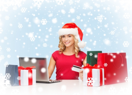 christmas, x-mas, online shopping concept - woman in santa helper hat with gift boxes, bags, laptop computer and credit card photo