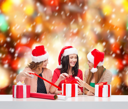 three gift boxes: christmas, x-mas, winter, happiness concept - three smiling women in santa helper hats with gift boxes and wrapping paper