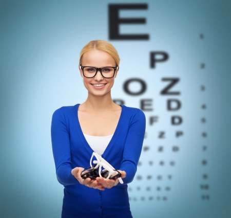 health care decisions: vision and health concept - smiling woman in casual clothes wearing and holding eyeglasses Stock Photo
