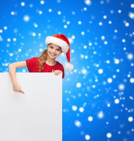 christmas, x-mas, people, advertisement, sale concept - happy girl child in santa helper hat with blank white board photo