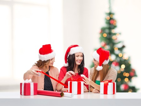 christmas, x-mas, winter, happiness concept - three smiling women in santa helper hats with gift boxes and wrapping paper photo