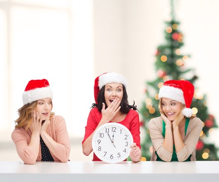 christmas, x-mas, winter, happiness concept - three smiling women in santa helper hats with clock showing 12 Stock Photo - 24014401