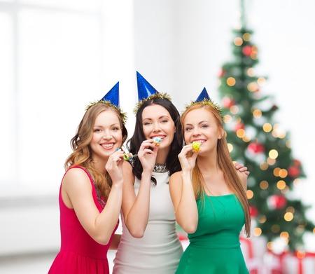 お祝い、友達、独身パーティー、誕生日のコンセプト - 青い帽子を身に着けている支持角を吹いている 3 つの笑みを浮かべて女性 写真素材