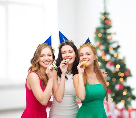 celebration, friends, bachelorette party, birthday concept - three smiling women wearing blue hats and blowing favor horns photo