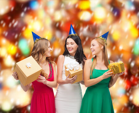 friends party: celebration, friends, bachelorette party, birthday concept - three smiling women wearing blue hats with gift boxes