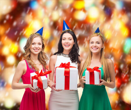 celebration, friends, bachelorette party, birthday concept - three smiling women wearing blue hats with gift boxes photo