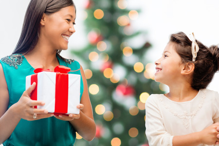 holidays, presents, christmas, x-mas concept - happy mother and child girl with gift box photo