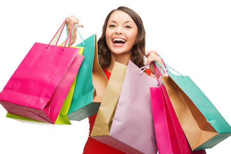 carrying girl: shopping, sale, gifts, christmas, x-mas concept - smiling woman in red dress with colorful shopping bags