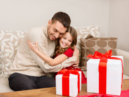 daugther: family, christmas, x-mas, winter, happiness and people concept - smiling father and daughter hugging Stock Photo