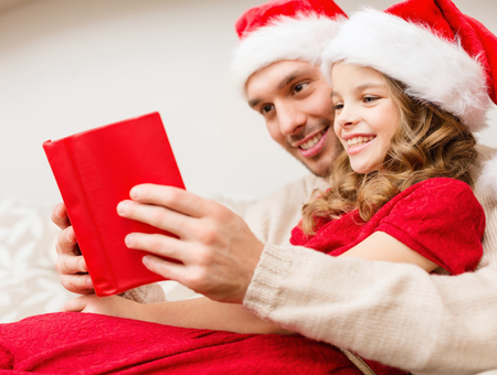 daugther: family, christmas, x-mas, winter, happiness and people concept - smiling father and daughter in santa helper hats reading book