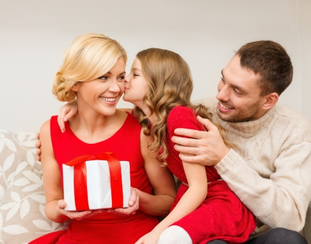 daugther: family, christmas, x-mas, winter, happiness and people concept - adorable child kisses her mother and gives present Stock Photo