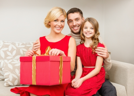 little girl surprised: family, christmas, x-mas, winter, happiness and people concept - happy family opening Stock Photo