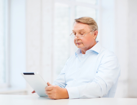 business, office, oldness, school and education concept - old man wearing eyeglasses with tablet computer at home photo