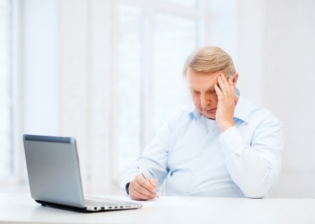 business, tax, office, school and education concept - old man filling a form at home photo