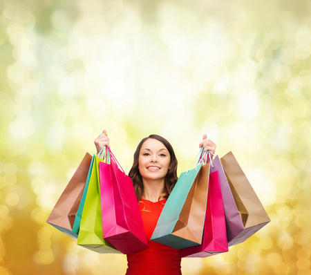 shopaholics: shopping, sale, gifts, christmas, x-mas concept - smiling woman in red dress with colorful shopping bags